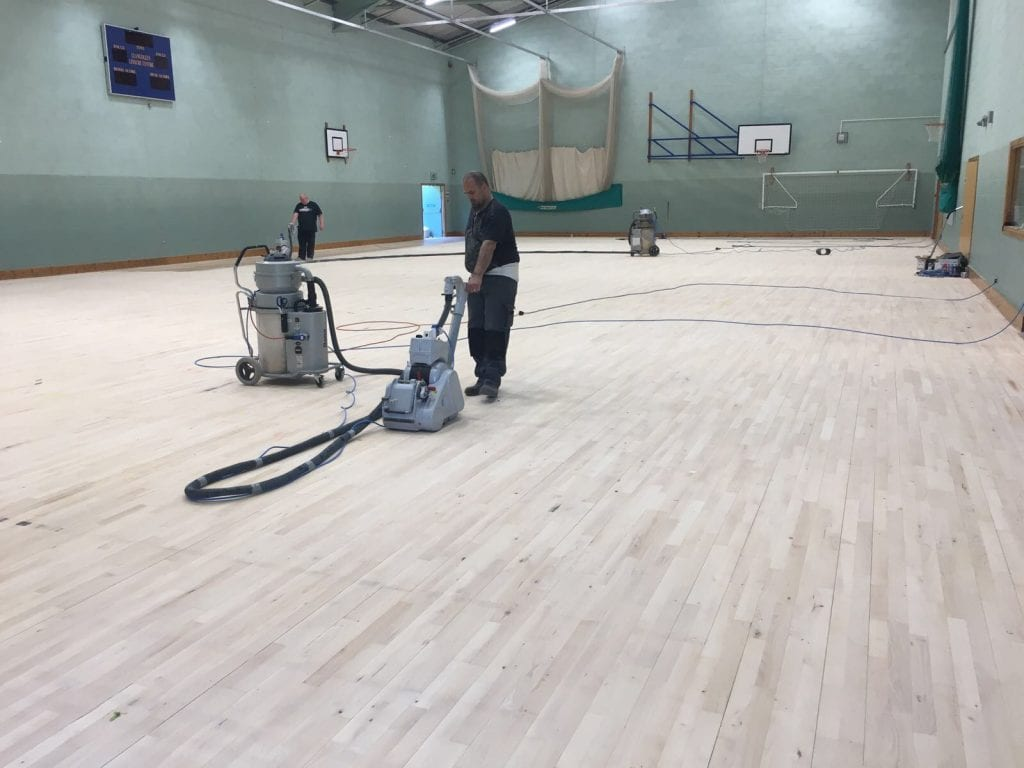 installation of Indoor timber sports hall floor with court markings for leisure centre