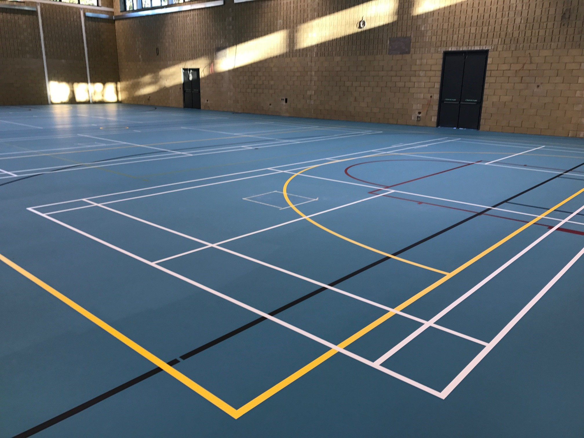 School sports hall blue Pulastic floor installation and court markings by Sports Surfaces UK