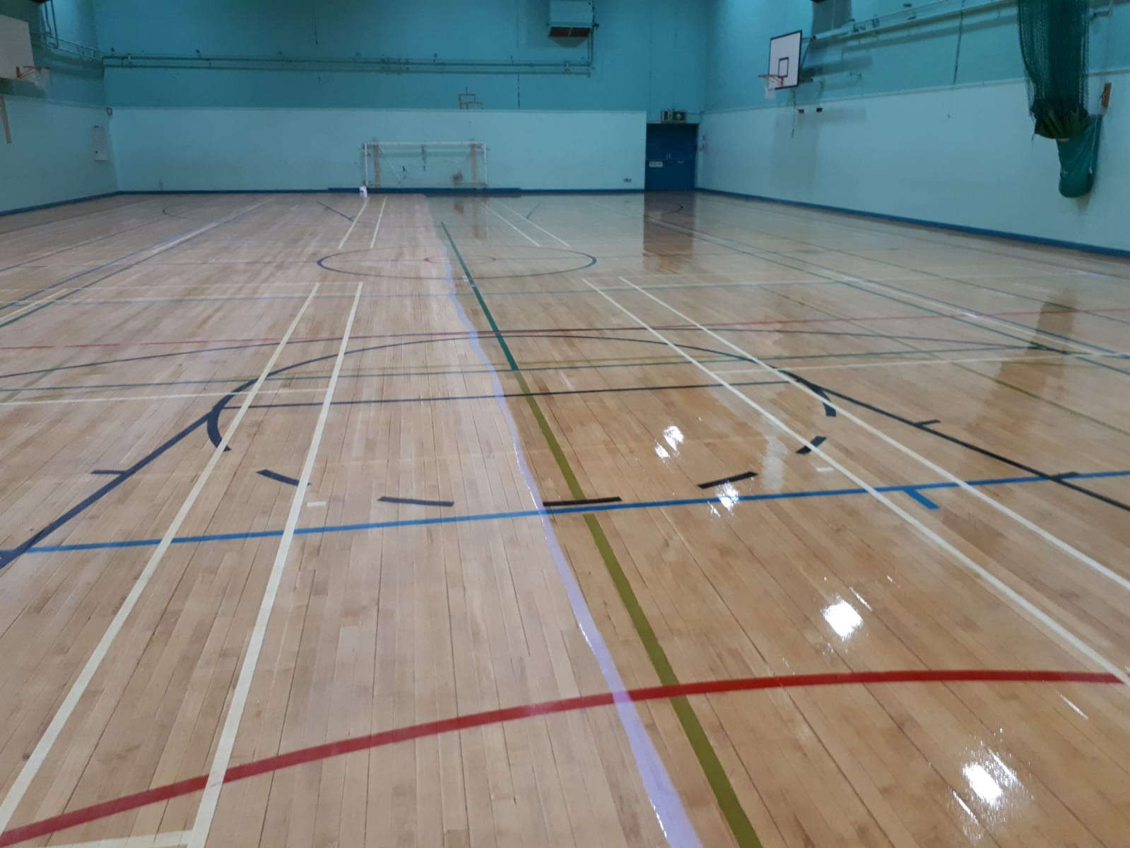 Castell Alun High School in Wrexham. The team replaced defective sections of the timber floor, scrubbed and applied a clear polyurethane seal and finally re-marked the netball courts.